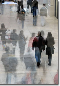 Crowd of shoppers in shopping mall. Two images overlaid to give ghosting effect. photo